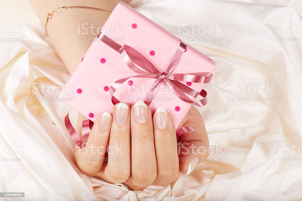 Hand with french manicured nails holding a gift box stock photo