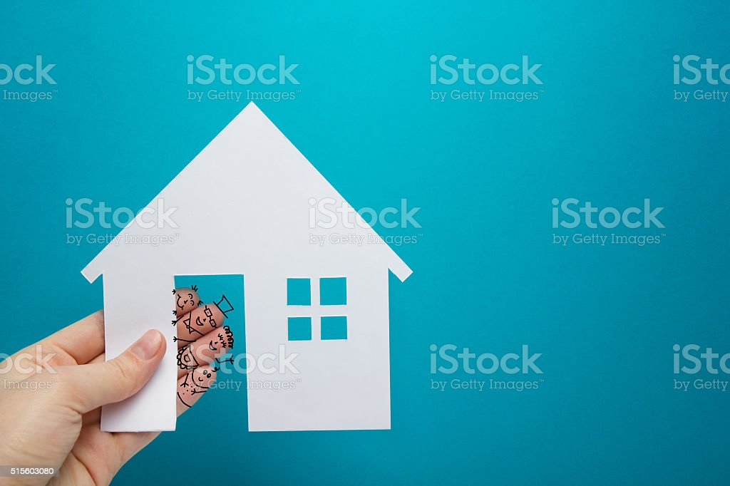Hand with funny fingers holding white paper house figure on stock photo