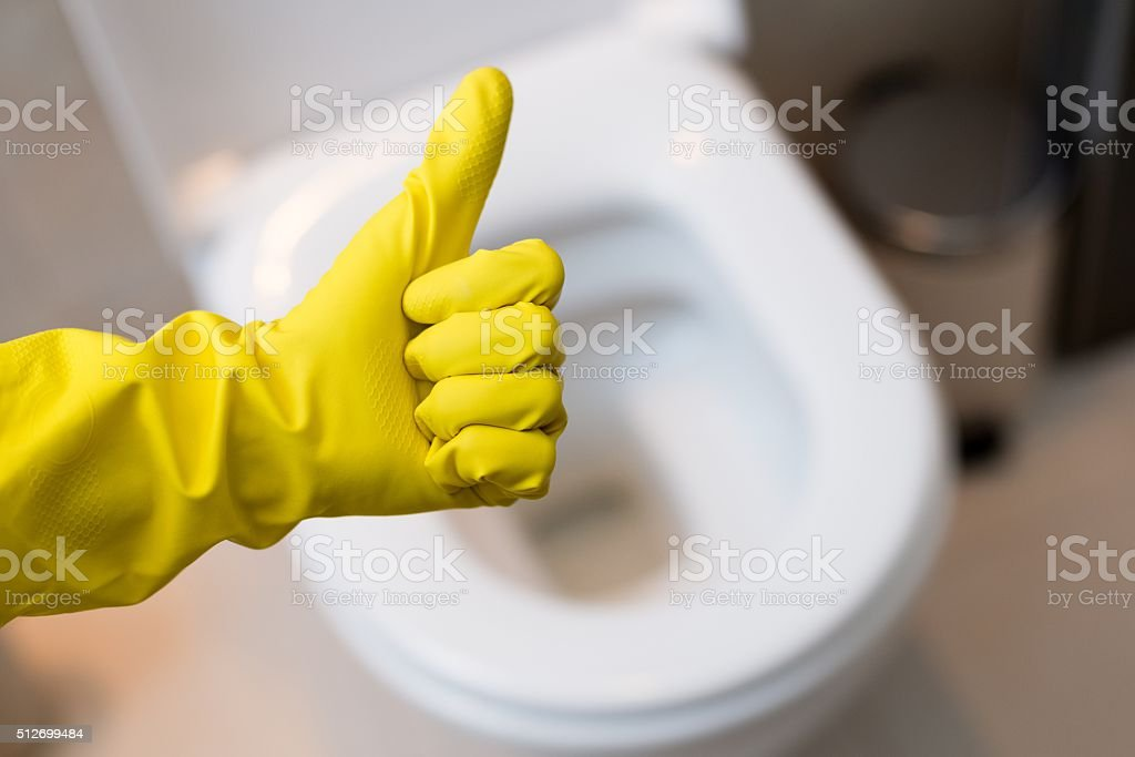 hand with glove showing thumb up sign against clean toilet stock photo