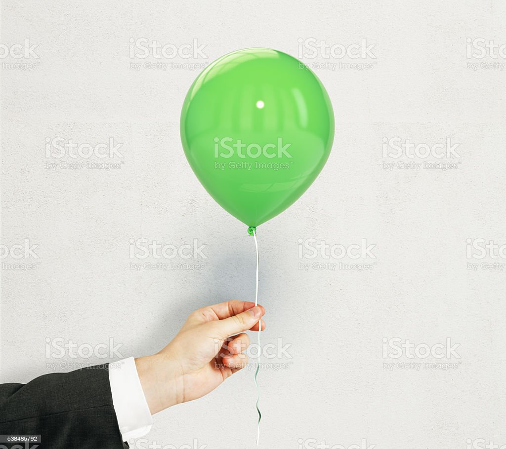 Hand with green balloon stock photo