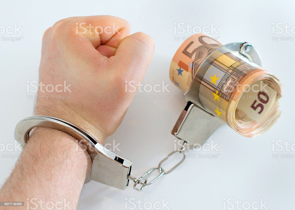 Hand with handcuffs and money. Bribery concept. stock photo