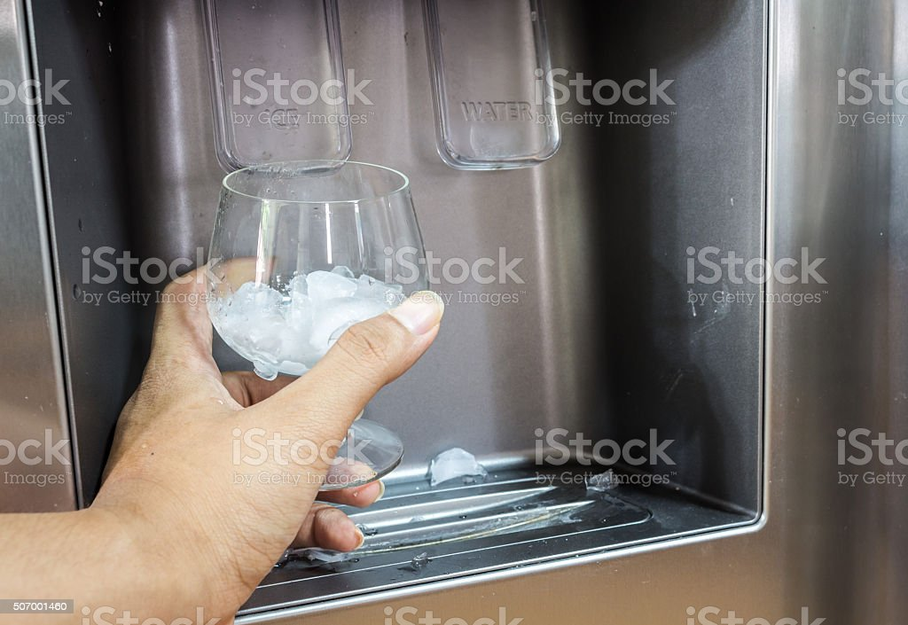 Hand with ice dispenser and glass stock photo