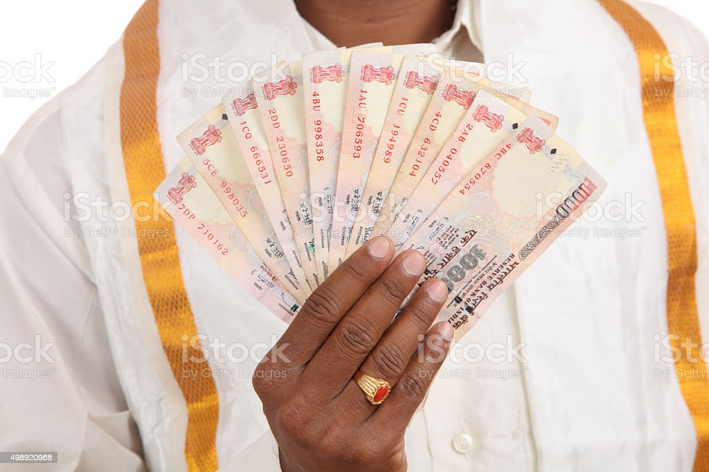 Hand with Indian thousand rupee notes stock photo
