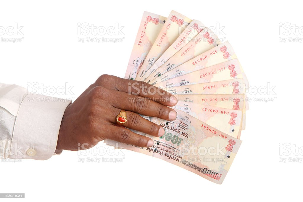 Hand with Indian thousand rupee notes. stock photo