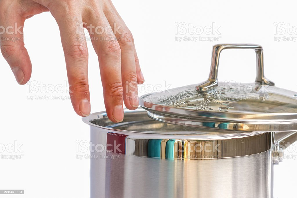 Hand with injuries above boiling water in the pot stock photo