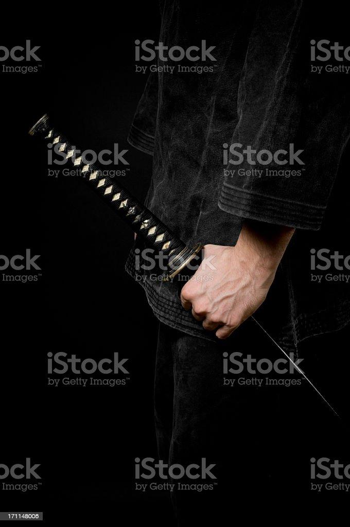 Hand with katana sword, black background stock photo