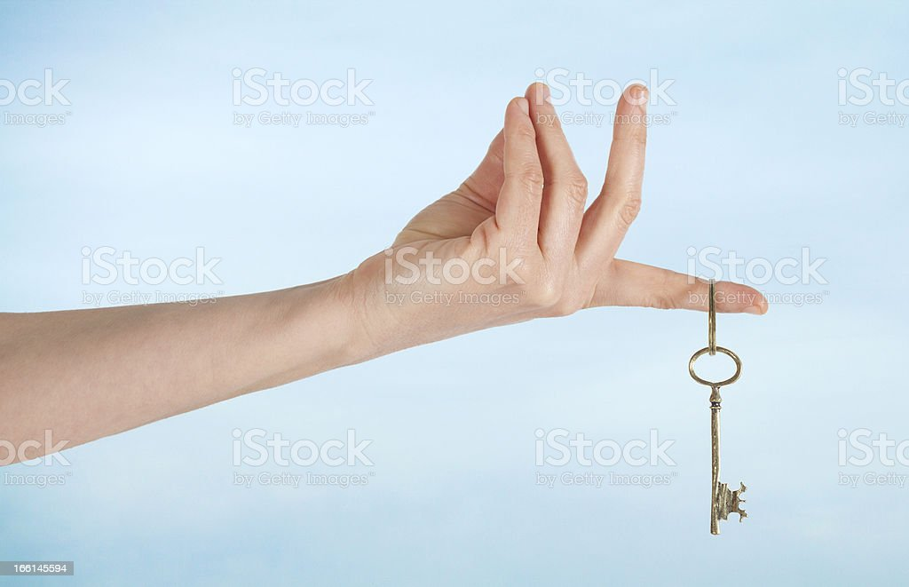 Hand with keys on sky background stock photo