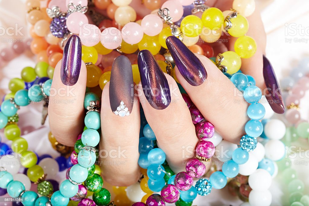 Hand with long artificial manicured nails stock photo