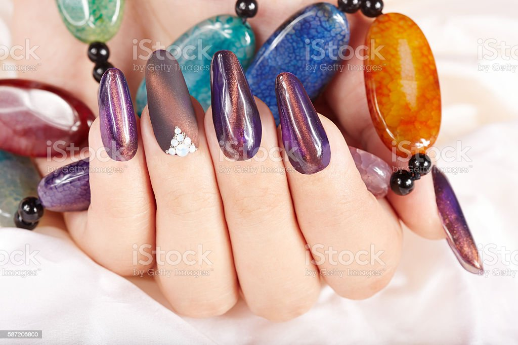 Hand with long purple artificial manicured nails holding a necklace