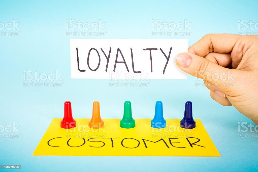 Hand with loyalty message over multicolored pawn pieces. stock photo