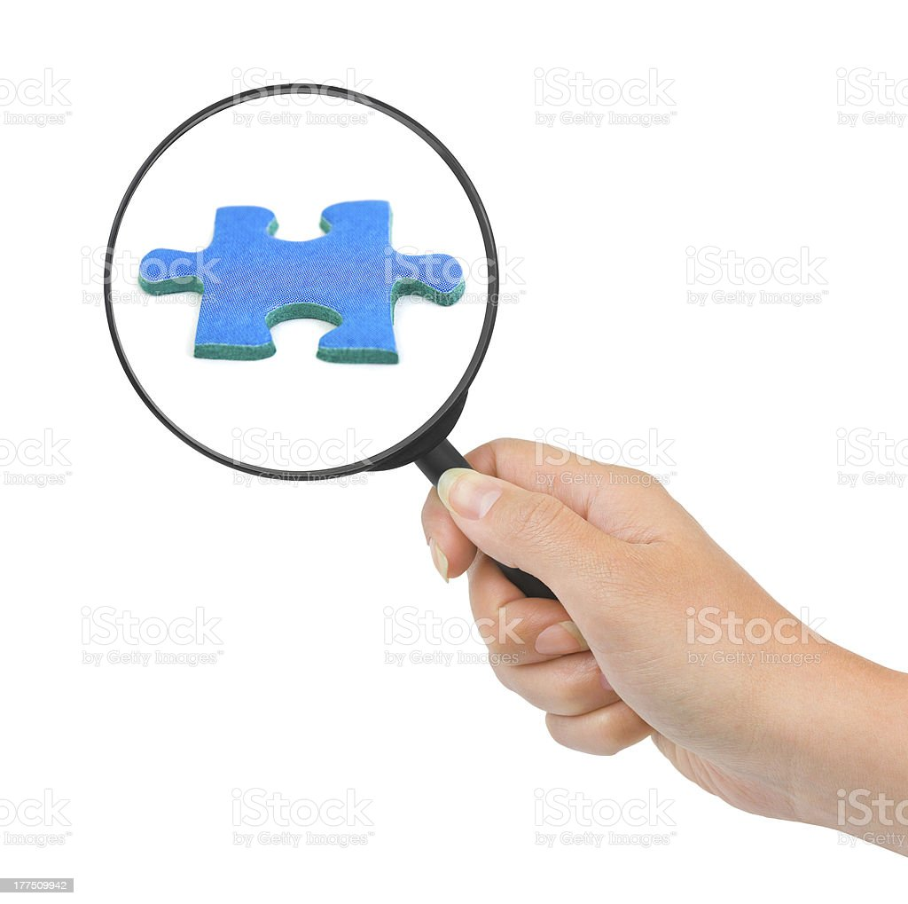 Hand with magnifying glass and puzzle royalty-free stock photo