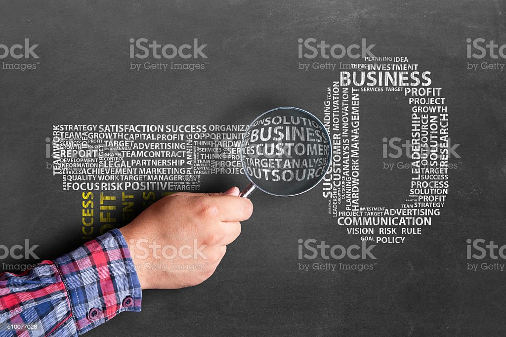 Hand with magnifying glass focusing on 'business' on word cloud stock photo