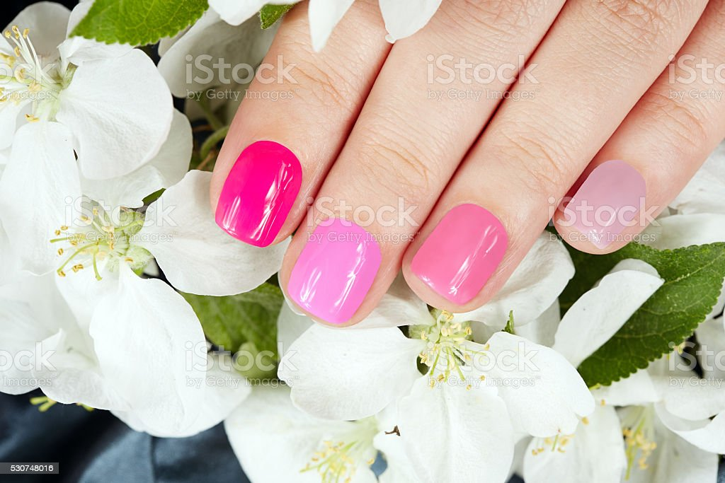 Hand with manicured nails on flowers background stock photo