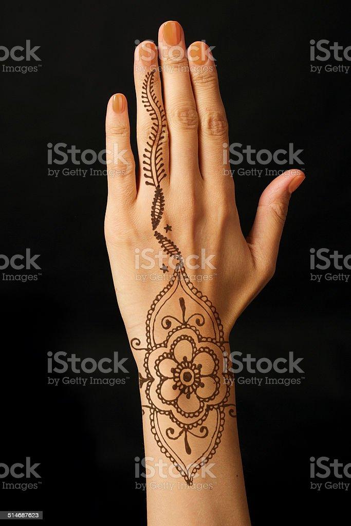 hand with mehendi on black background stock photo