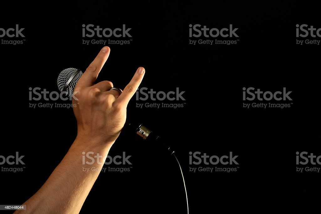 Hand with microphone and devil horns isolated on black royalty-free stock photo