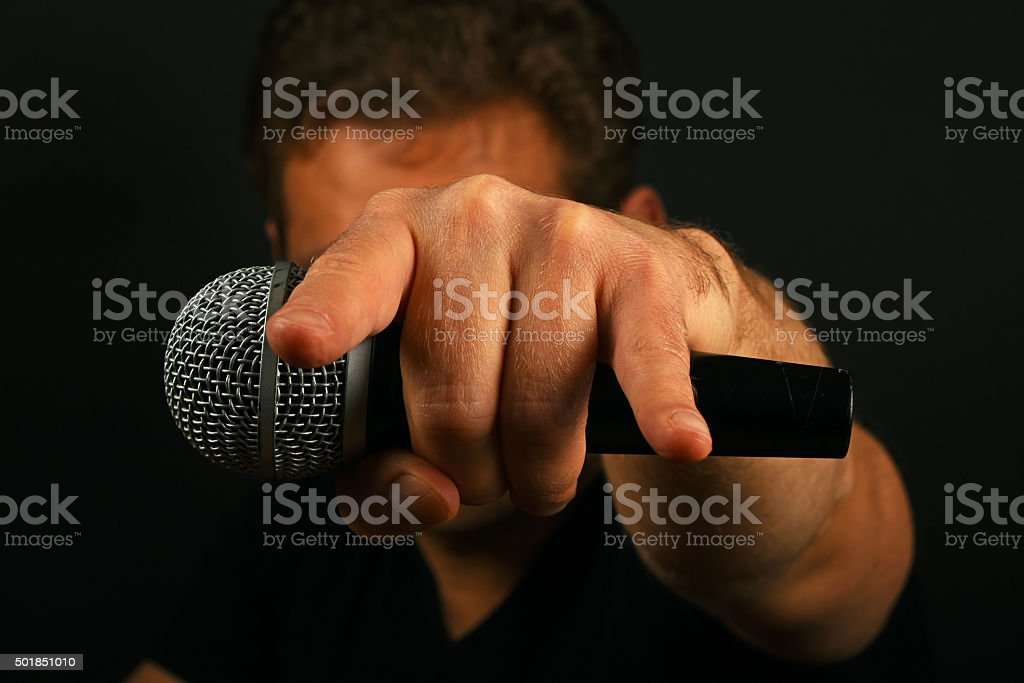 Hand with microphone and devil horns on black royalty-free stock photo