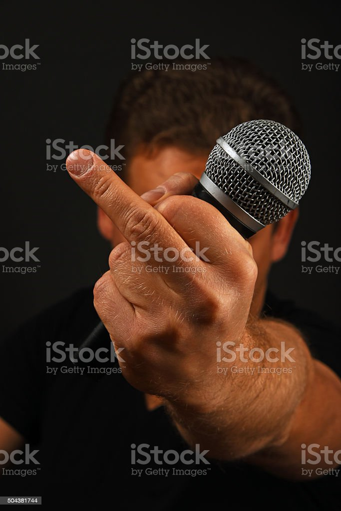 Hand with microphone and fuck off finger on black royalty-free stock photo