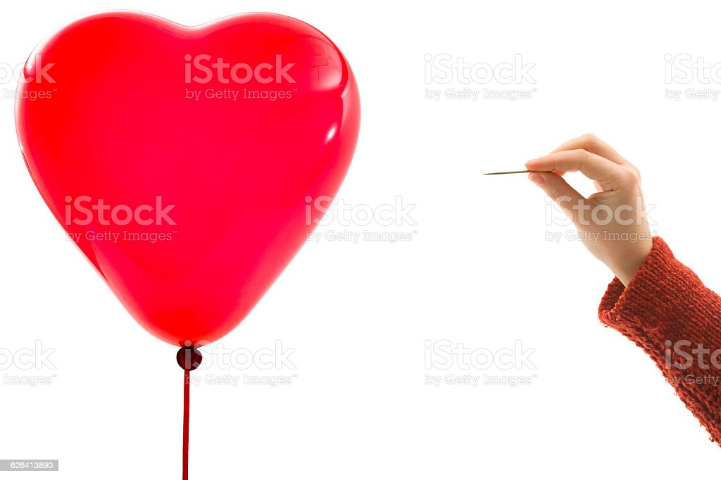 Hand with needle and heart balloon stock photo