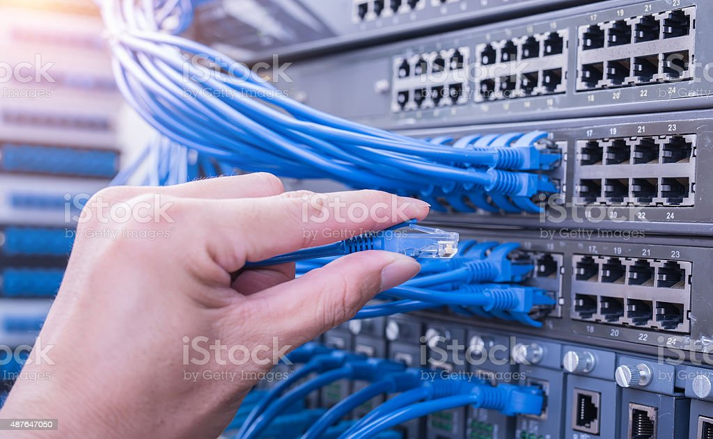 hand with network cable in a technology data center stock photo