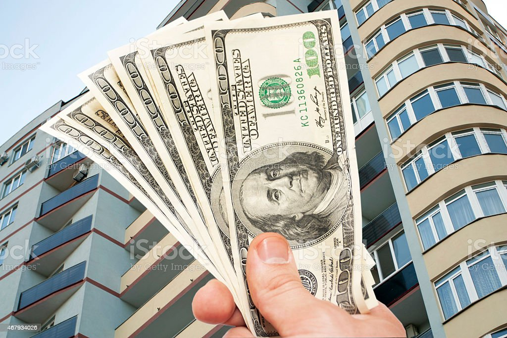 Hand with notes of dollars against the Residential building stock photo