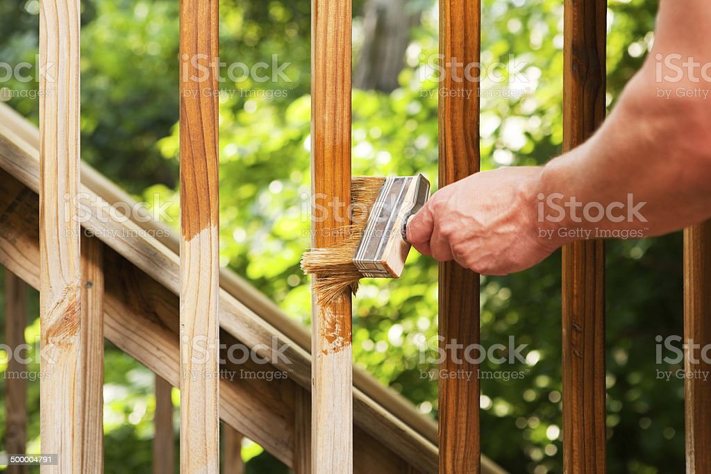 Hand with Paintbrush Staining Wood Deck Railing stock photo