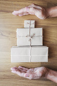 Hand with parcel gift box wrapped with hands carrying