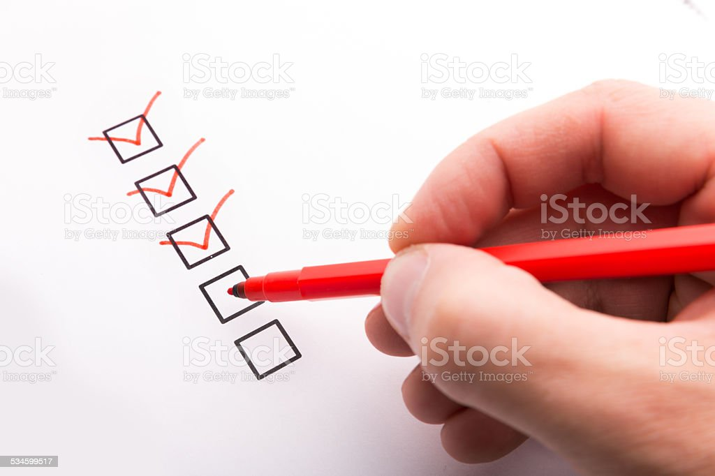 Hand with pen and check boxes stock photo
