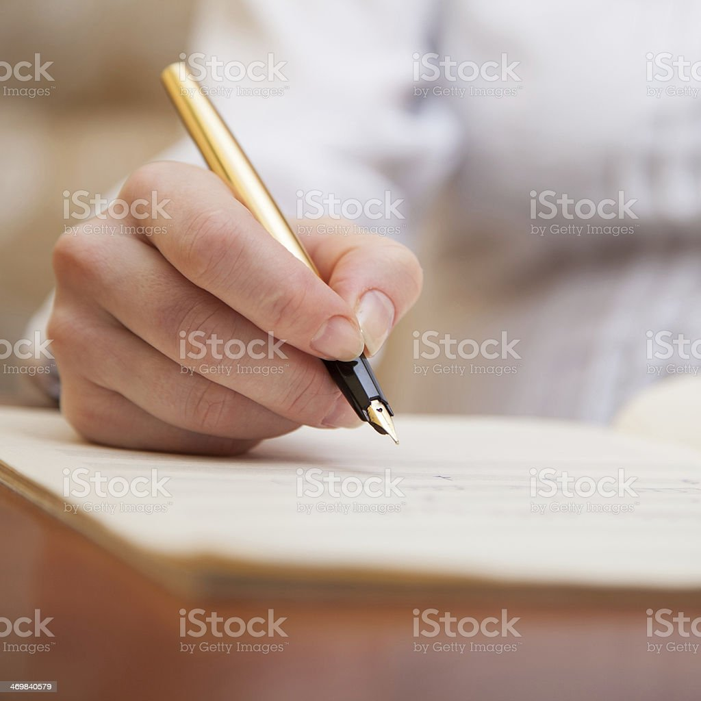 Hand with pen and music sheet royalty-free stock photo