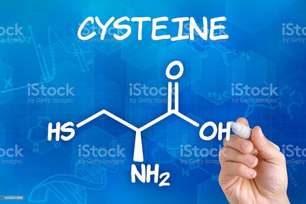 Hand with pen drawing the chemical formula of cysteine stock photo