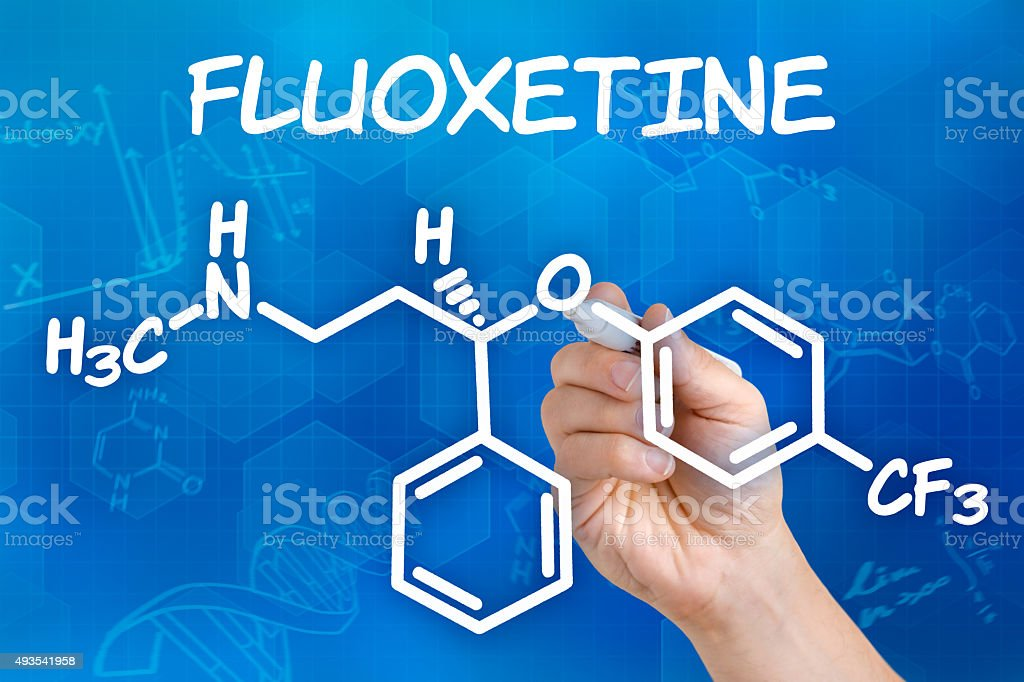 Hand with pen drawing the chemical formula of Fluoxetine stock photo