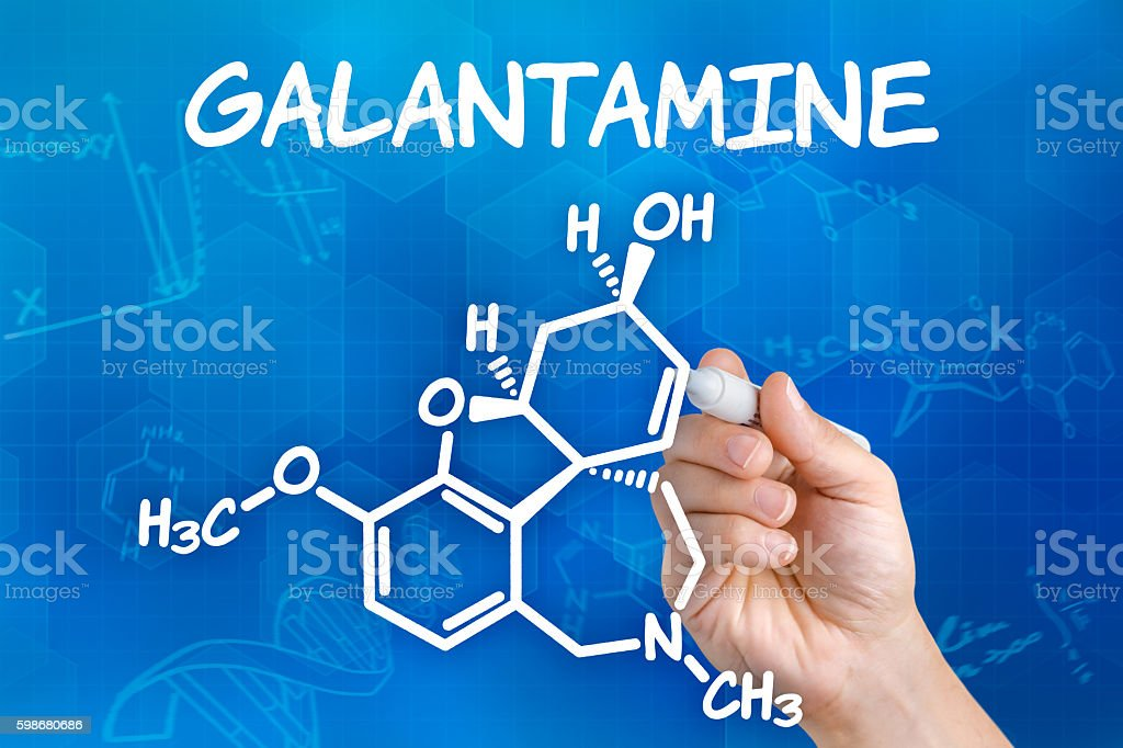 Hand with pen drawing the chemical formula of Galantamine stock photo