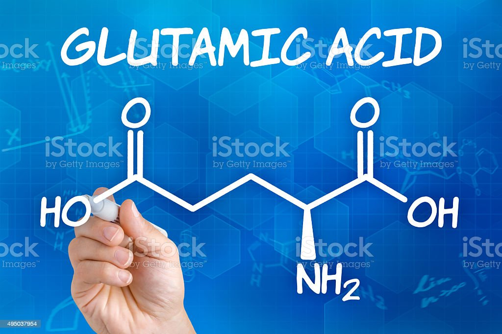 Hand with pen drawing the chemical formula of glutamic acid stock photo