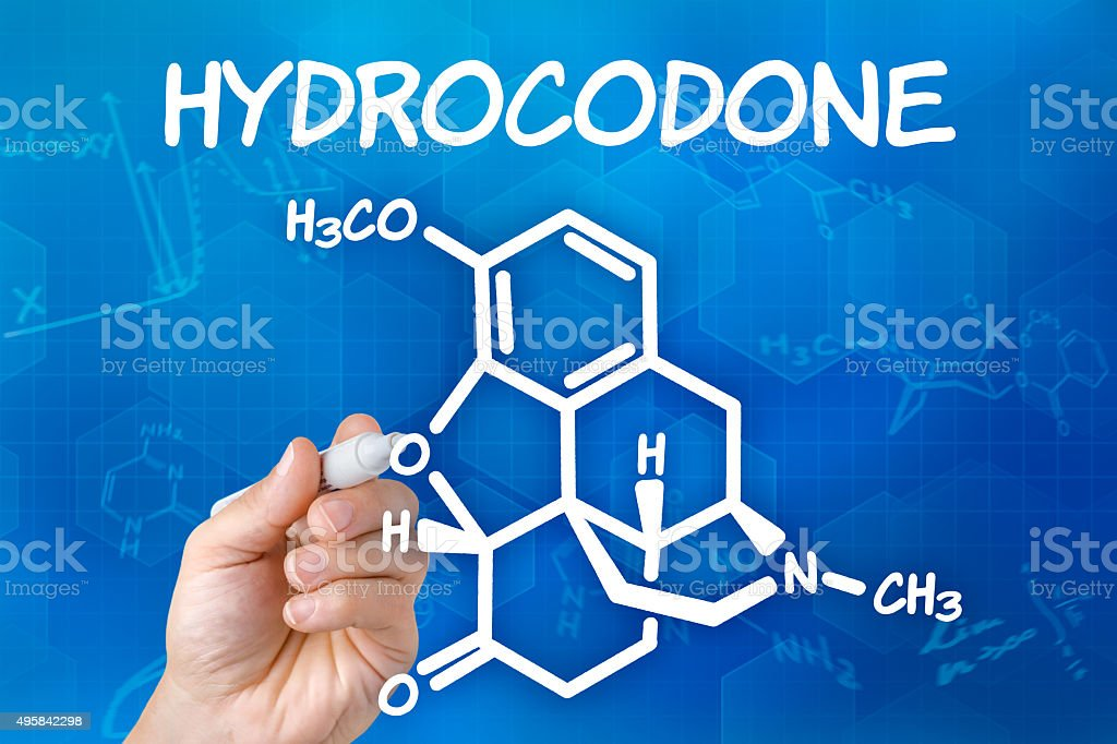 Hand with pen drawing the chemical formula of Hydrocodone stock photo