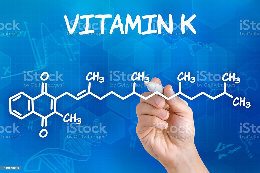 Hand with pen drawing the chemical formula of Vitamin K stock photo