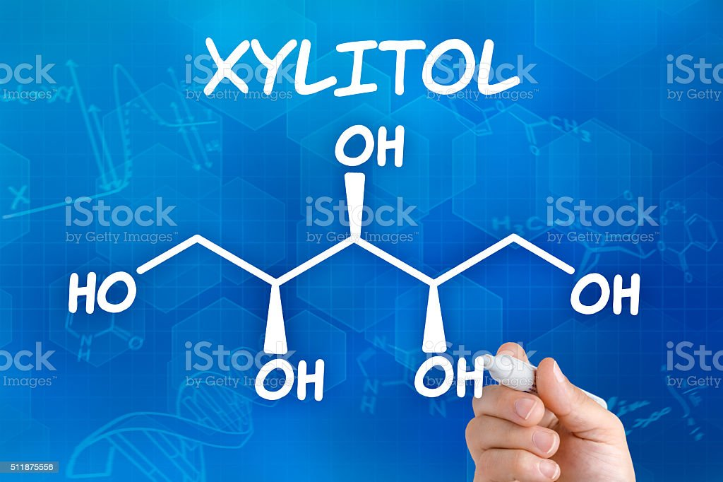 Hand with pen drawing the chemical formula of Xylitol stock photo