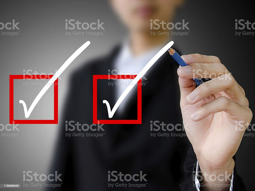 hand with pen mark the check boxes. stock photo