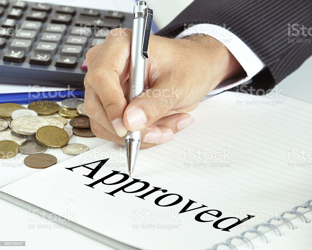 Hand with pen pointing to Approved word on the paper stock photo