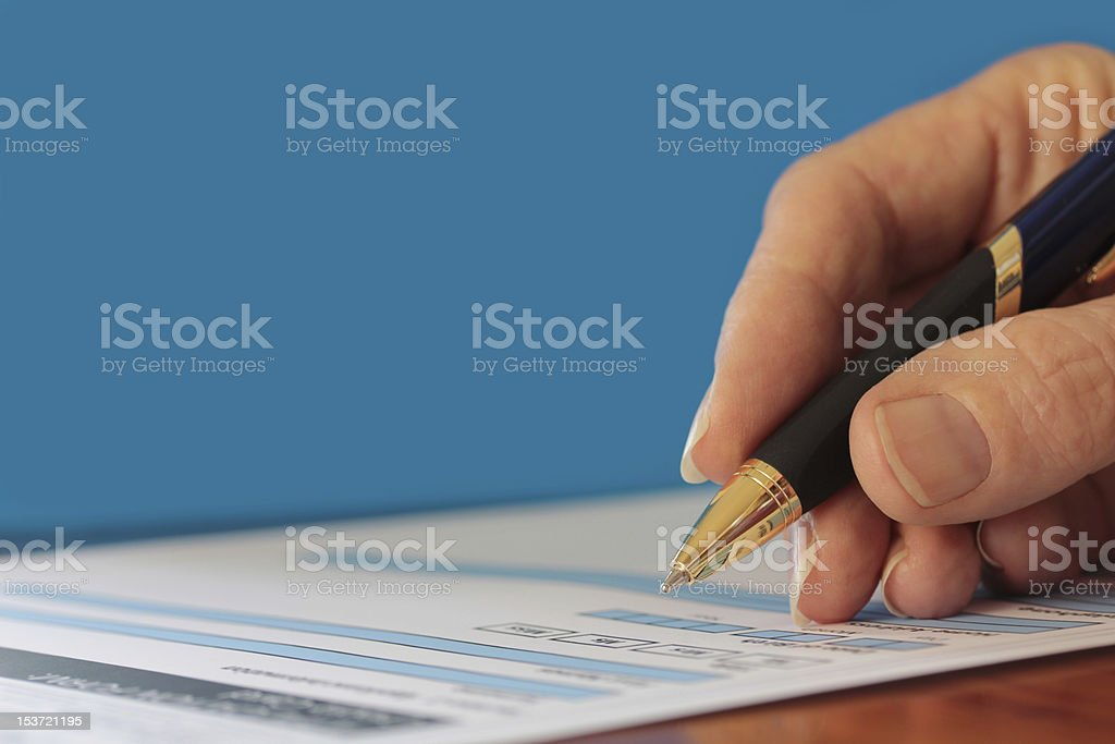 Hand with Pen Signing Form Closeup on Blue Background royalty-free stock photo