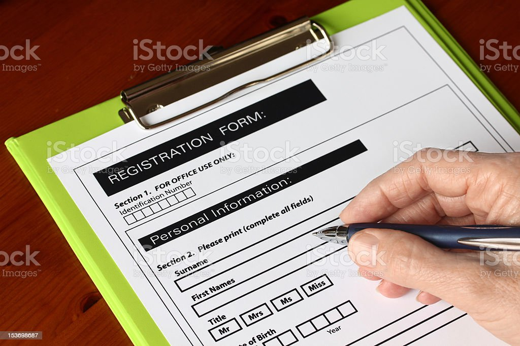 Hand with Pen Signing Form on Green Clipboard royalty-free stock photo