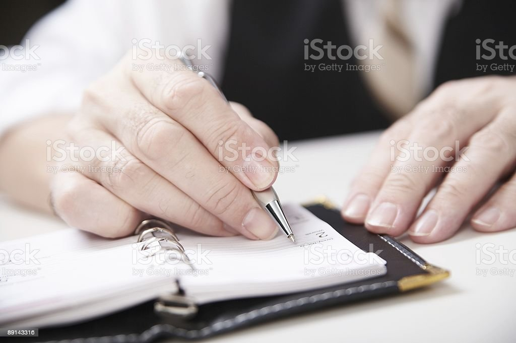 Hand with pen writing on a small notebook royalty-free stock photo