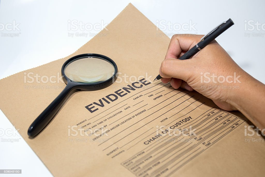 hand with pen writing on evidence paper with magnifying glass stock photo