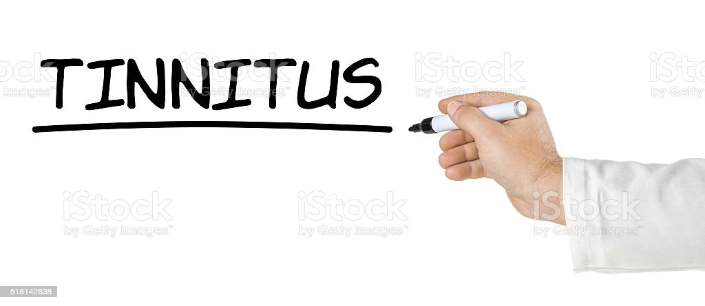 Hand with pen writing the word Tinnitus stock photo
