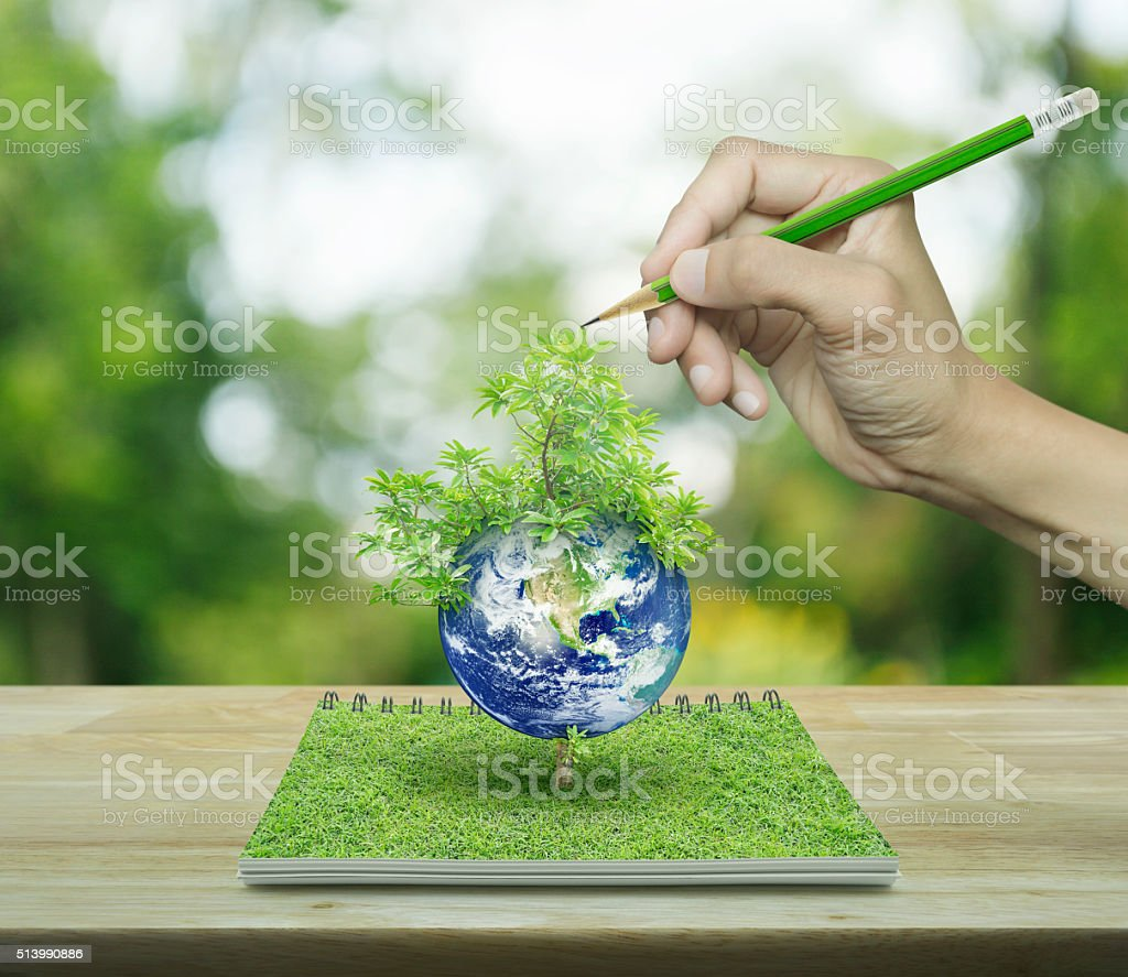 Hand with pencil drawing planet and tree, ecological concept stock photo