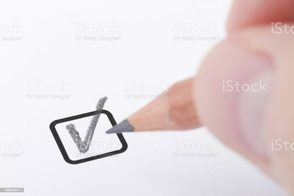 hand with pencil writing 'check mark' stock photo