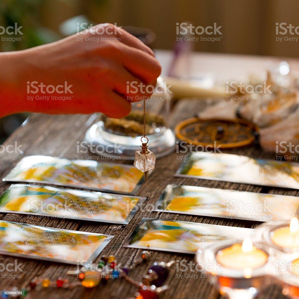 Hand with pendulum over tarot cards stock photo
