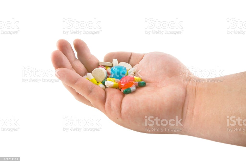 Hand with pills and tablets isolated on white background royalty-free stock photo