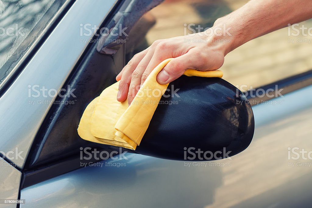 hand with rag polish the side mirror of car stock photo