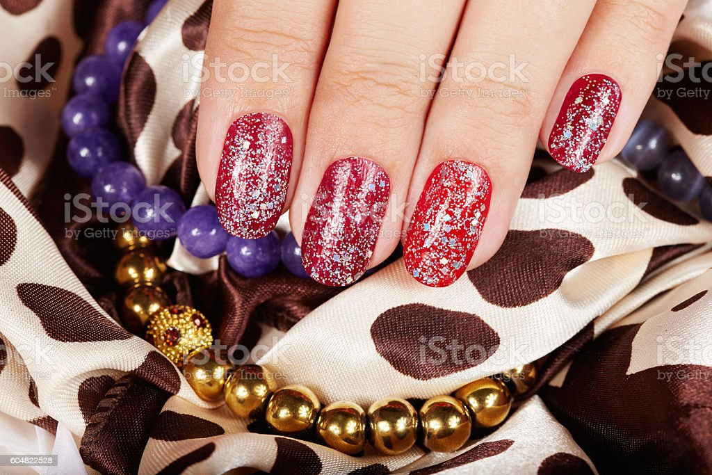 Hand with beautiful red manicured nails
