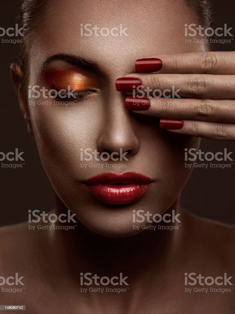 A hand with red nails blocking the left eye of a pretty lady royalty-free stock photo