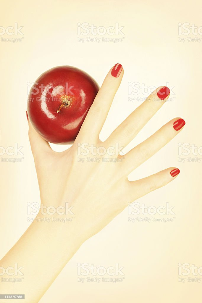 Hand with red nails manicure and apple. royalty-free stock photo